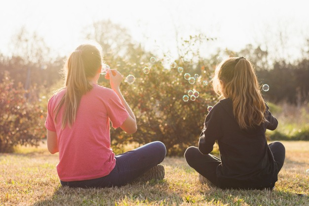 gallery/rear-view-of-two-girl-sitting-on-green-grass-blowing-bubbles_23-2147873650